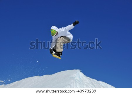a snowboarder performing a jump backwards trailing snow, against a clear blue sky