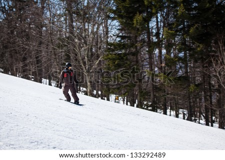 A snowboarder rides down the slopes of Snowshoe Mountain, WV. - stock photo