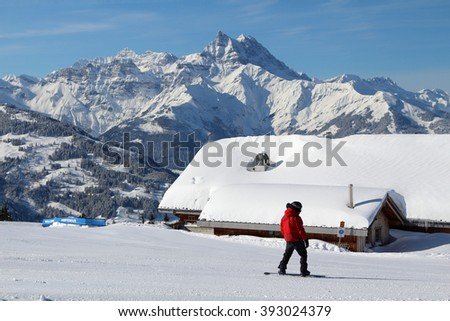 A snowboarder rides past a restaurant/bar in a luxury ski resort in the Swiss Alps in Villars, Switzerland. - stock photo