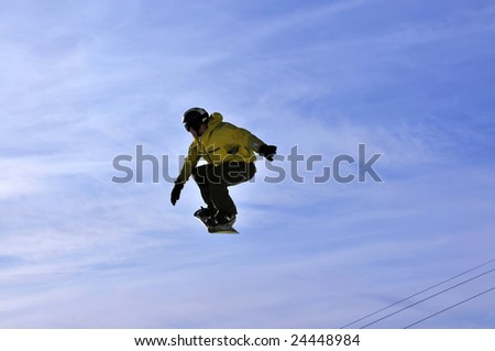 A snowboarder showing good balance on a high jump flies towards the sun