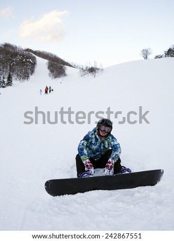 A snowboarder sitting on snow. - stock photo