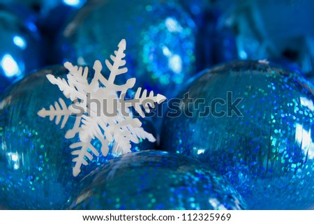 A snowflake rests on blue sphere Christmas ornaments.