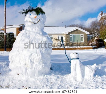 A snowman and snowdog smile for the camera - stock photo