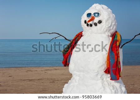 A snowman decides to go to the beach. - stock photo