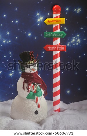 A snowman in the snow beneath a Santa sign on a long, starry North Pole night.  Intentionally dark for nighttime lighting. - stock photo