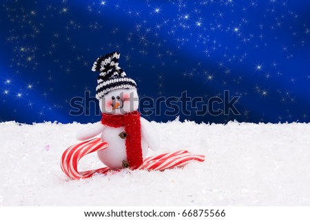 A snowman on a candy cane with a blue background, Winter Time - stock photo