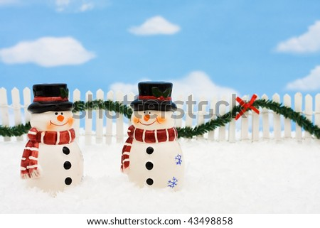 A snowman on a white picket fence with garland on a  sky background - stock photo