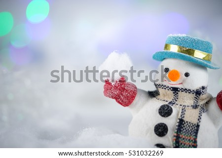 A snowman playing snow and decorations on bokeh background with copy space for season greeting Merry Christmas or Happy New Year.