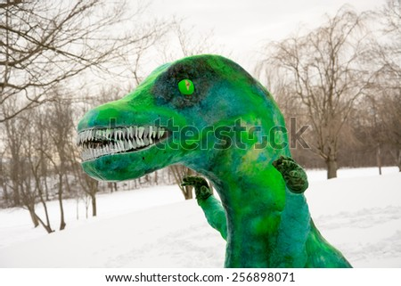 A snowman shaped like a dinosaur or monster painted green following a winter storm - stock photo