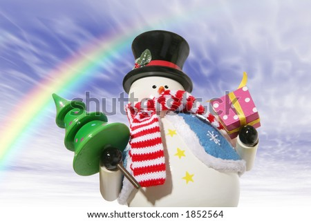 A snowman under the rainbow carrying a christmas tree and present - stock photo