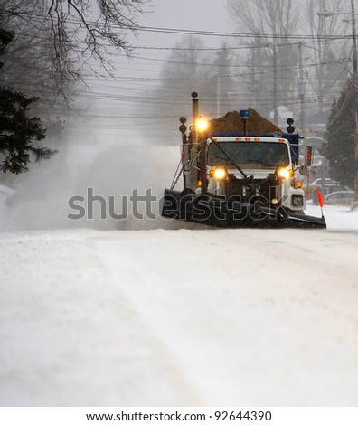 A snowplow in motion on a dark and snowy morning. - stock photo