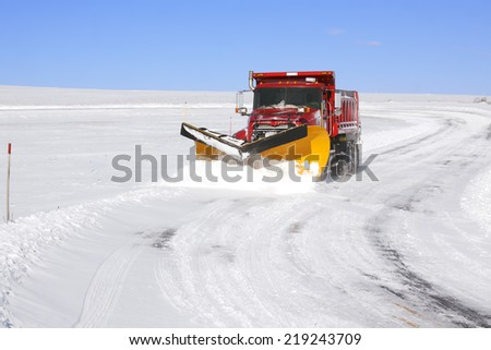 A snowplow truck removing snow from a winding rural road on bright winter day. - stock photo