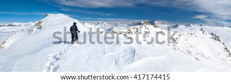 A snowshoer ascends to the top of a high mountain peak.