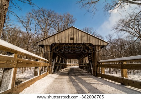 A snowy winter scene along a forest trail with a covered bridge crossing a creek. Found in Toledo Ohio's Wildwood Metropark. - stock photo