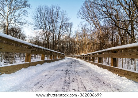 A snowy winter scene along a forest trail with a wooden bridge crossing a creek.  - stock photo
