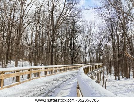 A snowy winter scene along an elevated winding boardwalk. Located in Toledo Ohio. - stock photo