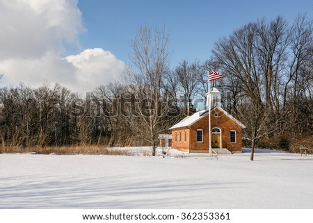 A snowy winter scene with an old historic one room school house.  - stock photo