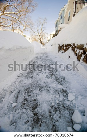 A snowy winter side walk cleared by shovel or snow blower in a nice tree lined neighborhood. - stock photo