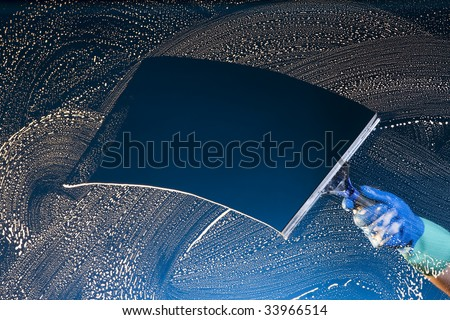 A soapy window with a squeegee cleaning the glass - stock photo