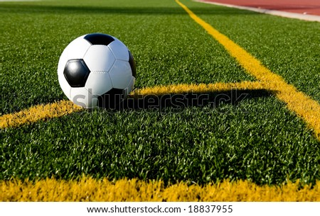 A soccer ball or football on a soccer field positioned for a corner kick - stock photo