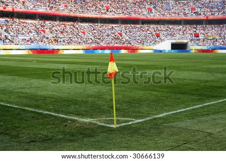 A soccer corner flag in a large stadium filled with spectators. - stock photo