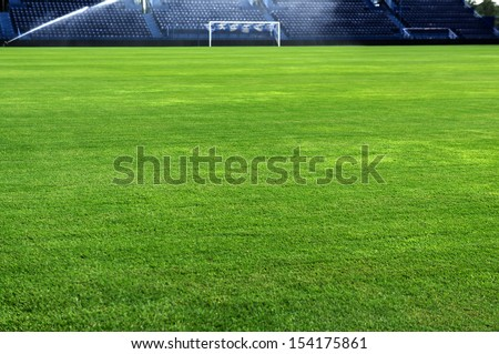 A soccer grass field is watered in the evening.  - stock photo