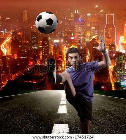 a soccer player in a street on the night - stock photo