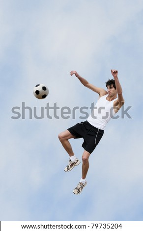 A soccer player jumps up into the air and hits the ball with his knee. - stock photo