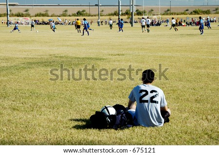 A soccer player relaxes while watching a game in process. - stock photo