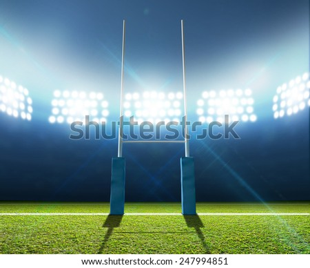 A soccer stadium with a marked green grass pitch with a soccer ball on the center mark at night under illuminated floodlights - stock photo