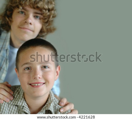 A soft and luminous portrait of an older teen supporting his younger kid brother - stock photo