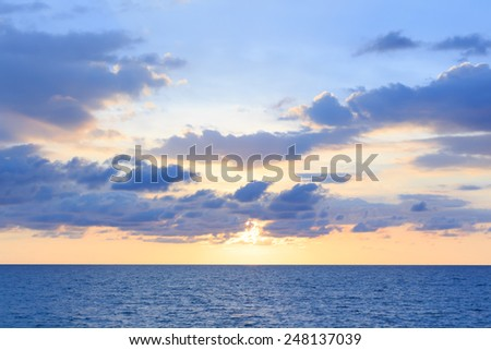 A soft cloud and sunset background with a pastel color blue to orange gradient.Blurred sea effect, pastel colors. - stock photo