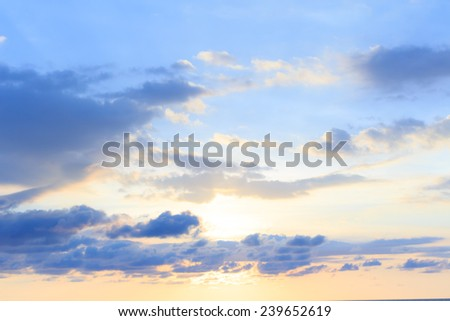 A soft cloud background with a pastel color blue to orange gradient. - stock photo