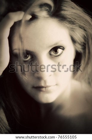 A soft, dreamy, portrait of a young woman gazing directly into camera in a vintage style. Very soft focus, eye is sharp. - stock photo