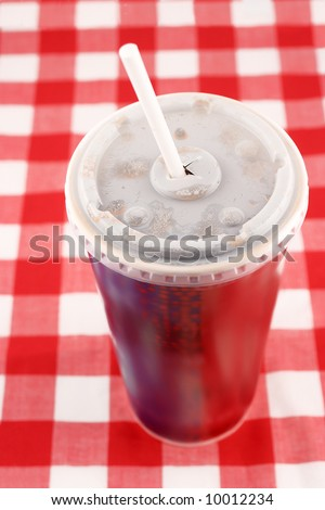 a soft drink in a takeout paper cup with lid and straw - stock photo