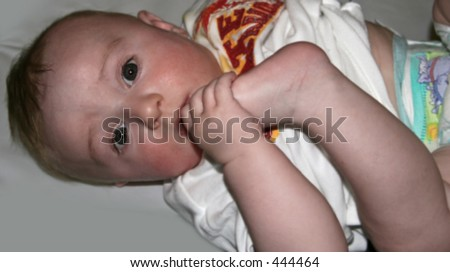 A soft focus picture of a five month old baby boy sucking his toes - soft focus - stock photo