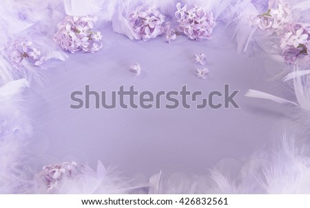 A soft, pastel background with a border of lilacs and feathers on a purple wood surface - stock photo