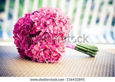 a soft pink hydrangea an rose bridal bouquet resting on a woven surface