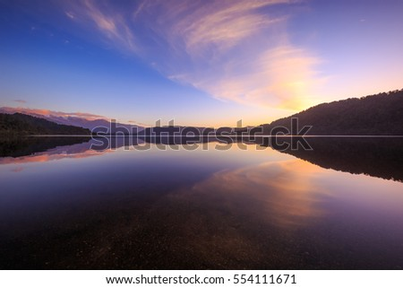 A soft reflection on a calm lake at sunset