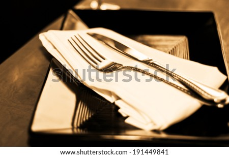 A soft toned image of a table setting with plate, napkin and utensils - stock photo
