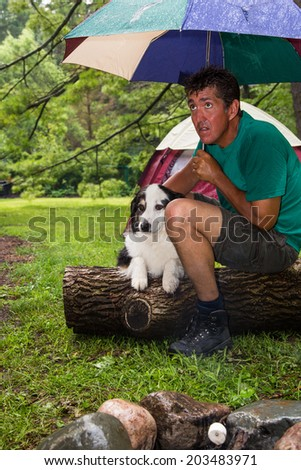 A soggy camper with his dog huddles under an umbrella anxiously waiting for the rain to stop - stock photo