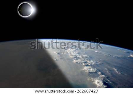 A solar eclipses partially shades the Earth below while the emerging sun lights the remainder of the planet. - Elements of this image furnished by NASA