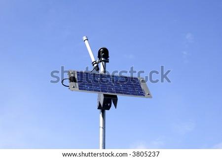 a solar panel on a pole against a blue sky - stock photo