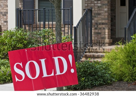A sold sign in front of a nice new home