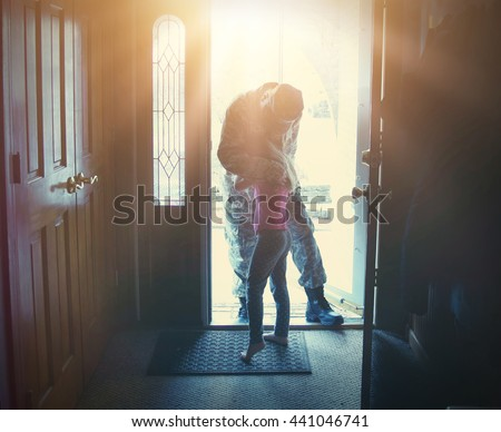 A soldier dad is coming home in the door and hugging his child for a love, family or reunited concept.