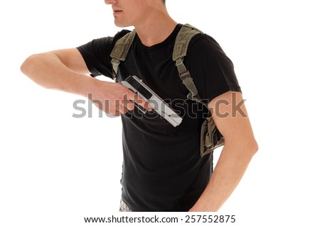 A soldier in black t-shirt, pulling his hand gun out of the holster, isolated on white background.  - stock photo