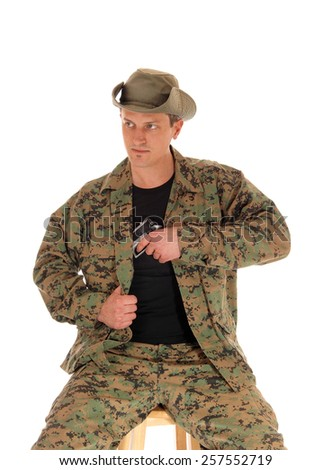 A soldier in camouflage uniform and hat pulling his hand gun out of the holster, isolated on white background.  - stock photo
