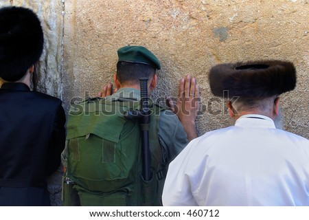 A soldier praying at the Wailing Wall - stock photo