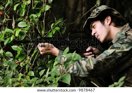 A soldier taking aim at his enemy from his concealed position