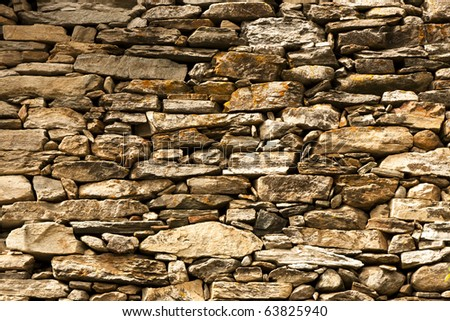 A solid stone wall of an italian alpine house. - stock photo